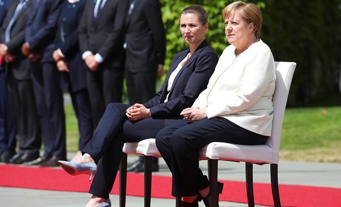 Merkel aparece sentada en honores militares tras temblores