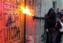 Mujeres pintan fachada y puerta de Palacio Nacional en protesta por feminicidios